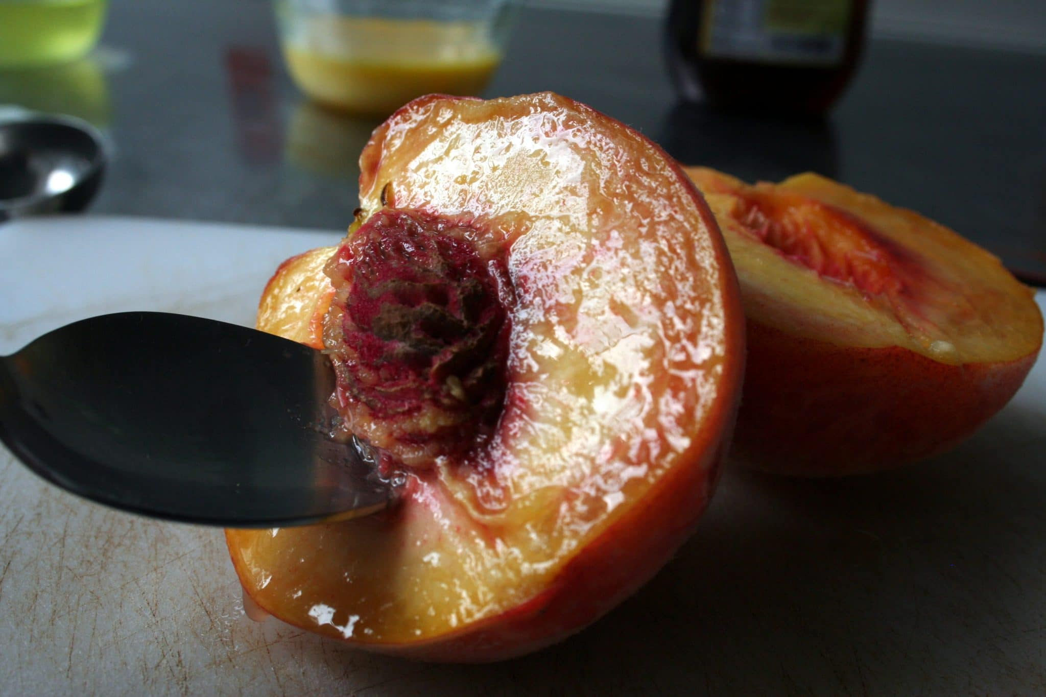 Spoon scooping pit out of peaches