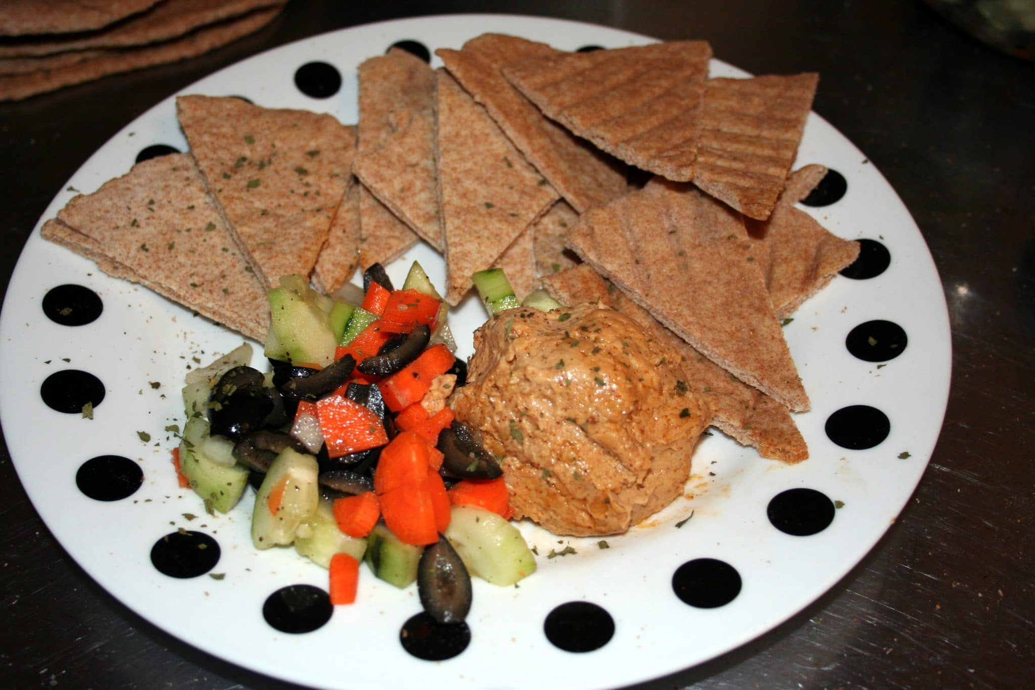 Vegan flatbread cut into triangles on plate with carrots, olives and zucchini