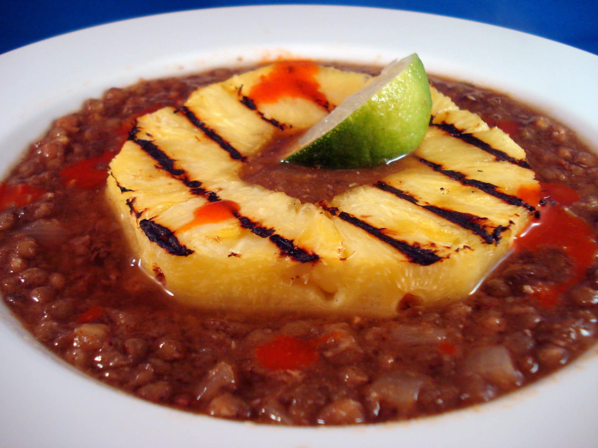 Bowl of lentil soup with grilled pineapple on top, with lime