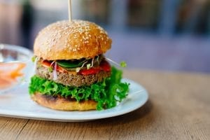 Veggie Burger on a bun with lettuce and tomato, sitting on a place