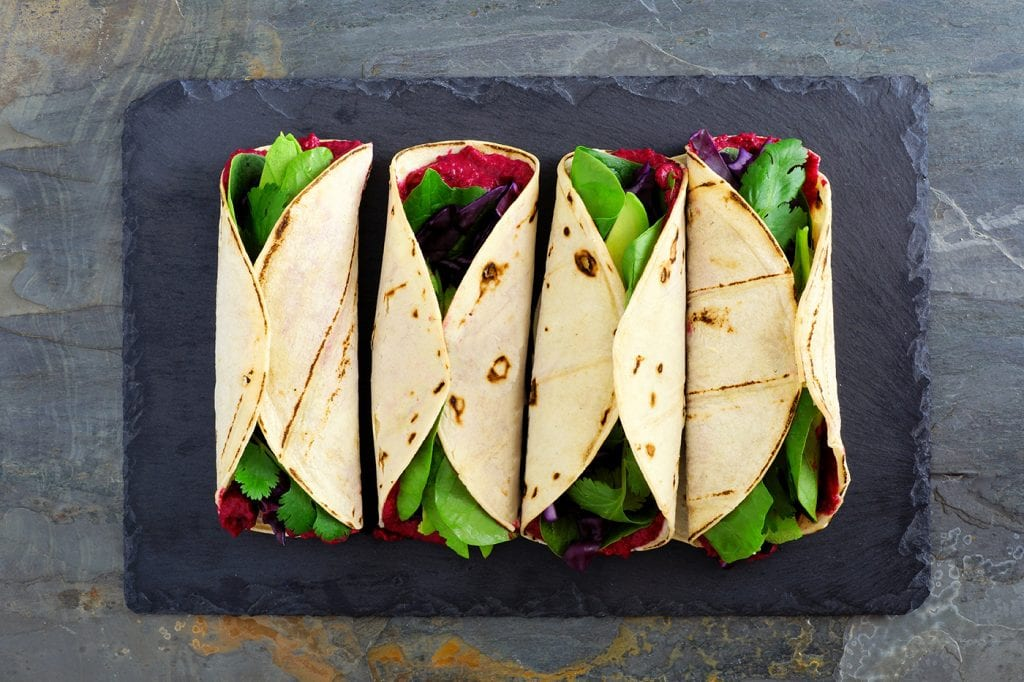 4 colorful wraps on astone plate with fresh greens and beets.